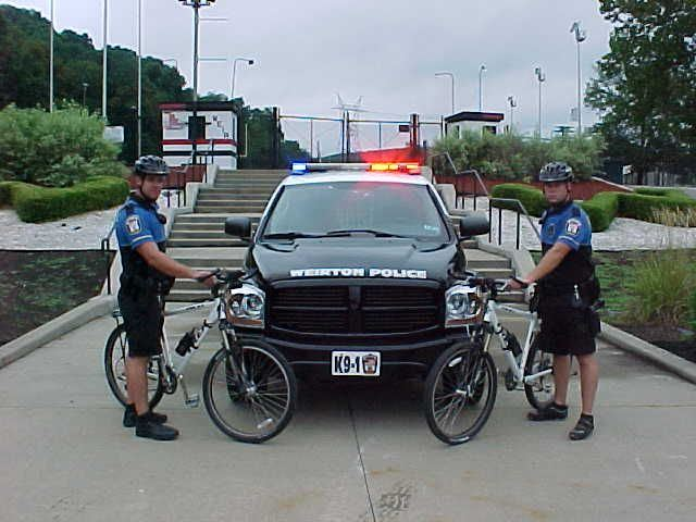 Two members of the Bicycle Patrol next to a squad car.